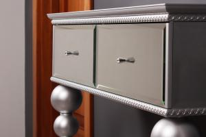 Turned legs, covered with silver Metallica, chest lined with bevelled mirror