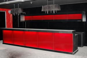 Bar counter, veneered with hard laminate, red glass front panels lit from behind